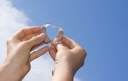 Showing a heart from hearing aids. Hands showing a heart shape from digital hearing aids in fron of a blue sky background royalty free stock image