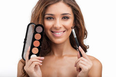 Showing her make-up stuff. Beautiful young women holding the mak Stock Photography