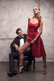 Showing her slender leg. Beautiful girl in red dress trying to seduce handsome man Stock Image