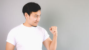 Showing his fist to inspire to fight. An asian man with white t-shirt and grey background Royalty Free Stock Images