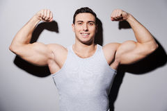 Showing his perfect muscles. Young muscular man showing his biceps and smiling while standing against grey background Royalty Free Stock Photo