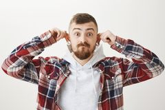 Showing his stretched ears and proud of cool flesh tunnels. Attractive urban european guy in modern stylish clothes. Pulling ears up, making silly and cute face Stock Photography