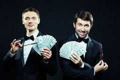 Showing how to earn. Portrait of two men in tuxedoes holding banknotes in hands Royalty Free Stock Photography