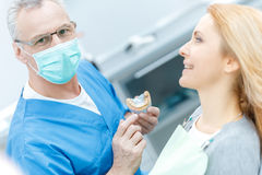 Showing jaws model to patient in dental clinic stock photo