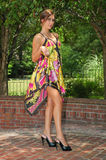 Showing a little leg. A young lady poses in a colorful flowing dress on a brick platform showing off a bit of her legs royalty free stock images