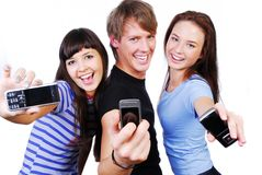 Showing mobile phones' screen. Two young woman and a man between them. They're showing mobile phones' screen. Isolated on white in studio Stock Photography