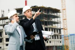 Showing new building. Photo of serious employee pointing at something with calling foreman standing near by Stock Photos