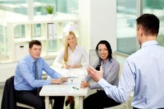 Showing new product. Businessman presenting new product or device to his smiling colleagues Royalty Free Stock Photos