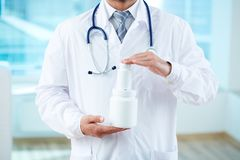 Showing new vitamins. Close-up of doctor holding two containers with vitamins Stock Images
