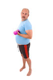 Showing off. Overweight man with big beerbelly is doing weight exercises royalty free stock image