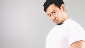 Showing off his chest to pretend that he is stronger. An asian man with white t-shirt and grey background royalty free stock images