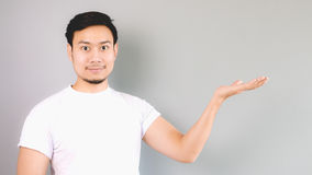 Showing or offering a content, product, copyspace. An asian man with white t-shirt and grey background royalty free stock photos