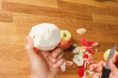 Showing a peeled apple. A hand holding a peeled apple over a pile of peelings Stock Images