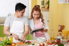 Showing recipe. Smiling young women showing video recipe on tablet computer to her boyfriend Stock Images
