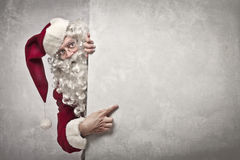 Showing Santa Claus. Santa Claus indicating something on a white wall