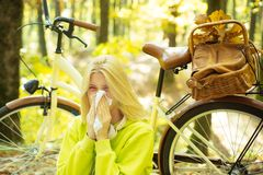 Showing sick woman sneezing at park. Sick girl with cold and flu standing outdoors. stock image