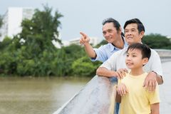 Showing something interesting. Middle-aged men showing something interesting to his father and son while standing on the bridge stock image