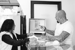 Showing a tattoo design. Male tattoo artist is showing the drawings in a computer to a young female customer before the tattoo session at the tattoo shop royalty free stock photo