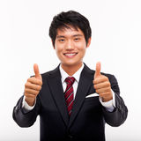 Showing thumb young Asian business man. Royalty Free Stock Images