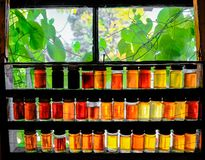 Jars of different strength Maple Syrups seen in a window at a Maple Syrup farm. Showing the various colours and strengths of maple syrup seen here at a farm in Stock Images