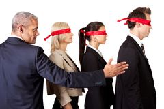 Showing the way. Businessman showing the way for group of disoriented businesspeople Royalty Free Stock Photos