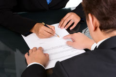 Showing where to sign. A business man is pointing a place where she should sign the agreement Royalty Free Stock Images