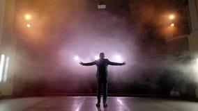 Showman представляет его выставку, распространяя его руки к сторонам Парень в фиолетовом лифчике и цилиндре яркое акции видеоматериалы