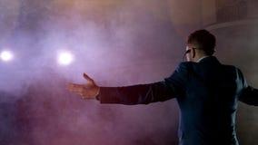 showman Actor, presentador o actor de sexo masculino joven en etapa Apoye, los brazos a los lados, humo en el fondo del proyector almacen de metraje de vídeo