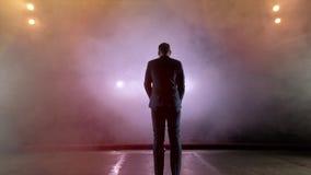 showman Anfitrião, apresentador ou ator masculino novo na fase Suporte, os braços aos lados, fumo no fundo do projetor vídeos de arquivo
