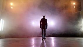 showman Anfitrião, apresentador ou ator masculino novo na fase Suporte, os braços aos lados, fumo no fundo do projetor filme