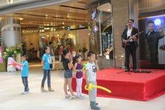 Showman europeo ed il suo piccolo pubblico asiatico a Shenzhen Fotografie Stock Libere da Diritti