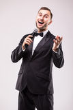 The Showman interviewer with emotions. Young elegant man holding microphone against white background. Royalty Free Stock Photo