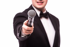 The Showman  interviewer. Young elegant man holding microphone Royalty Free Stock Photos