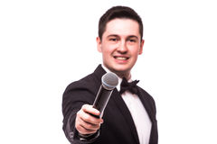 The Showman  interviewer. Young elegant man holding microphone against Royalty Free Stock Photography