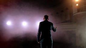 showman Młody męski artysta estradowy, podawca lub aktor na scenie, Popiera strony, ręki, dym na tle światło reflektorów zbiory wideo