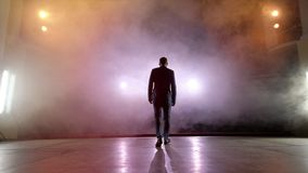 showman Młody męski artysta estradowy, podawca lub aktor na scenie, Popiera strony, ręki, dym na tle światło reflektorów zbiory