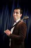 Showman with a microphone. Studio portrait of a funny showman with the microphone royalty free stock photos