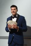 Showman with money. Happy handsome young brunet man holding a lot of money looking sideways while standing on blue wall background Royalty Free Stock Photography