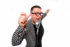 Showman singing in microphone with emotional gesture Stock Photo