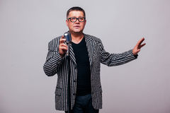 Showman singing in microphone with emotional gesture Royalty Free Stock Image