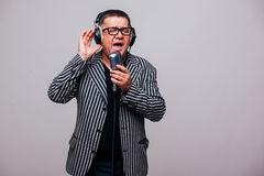 Showman singing in microphone with emotional gesture Royalty Free Stock Photography