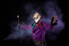 Showman spreading hands, show begins. The guy in the purple camisole and the cylinder. Showman spreading hands, show begins. Young male entertainer, presenter stock image