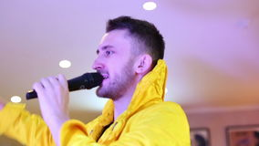 Showman in yellow fashionable suit speaks in a microphone.