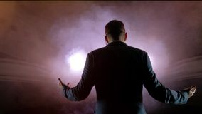 Showman. Young male entertainer, presenter or actor on stage. Back, arms to sides, smoke on background of spotlight. Rear view of a male public speaker