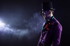 Showman. Young male entertainer, presenter or actor on stage. The guy in the purple camisole and the cylinder. Bright tailcoat, suit Royalty Free Stock Image