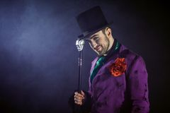Showman. Young male entertainer, presenter or actor on stage. The guy in the purple camisole and the cylinder. Bright tailcoat, suit stock photo