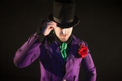 Showman. Young male entertainer, presenter or actor on stage. The guy in the purple camisole and the cylinder. Bright tailcoat, suit Royalty Free Stock Photography