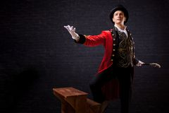 Showman. Young male entertainer, presenter or actor on stage. The guy in the red camisole and the cylinder. Bright tailcoat, suit stock photos