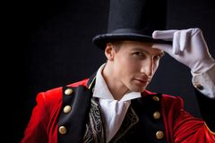 Showman. Young male entertainer, presenter or actor on stage. The guy in the red camisole and the cylinder. Bright tailcoat, suit stock photography