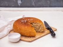 Shown is a section of round homemade freshly baked bread. Salt shaker with coarse salt and a large kitchen knife. In the background, a white cotton napkin on a stock photos